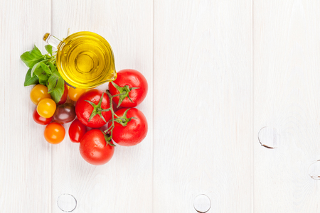 vegetables on white: Italian food cooking ingredients. Olive oil, tomatoes, basil on wooden table. Top view with copy space Stock Photo