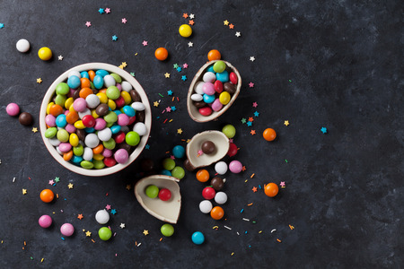 chocolate egg: Colorful candies and chocolate egg on stone background. Top view