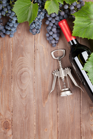 Red grape, wine bottle and corkscrew on wooden table. Top view with copy space Reklamní fotografie