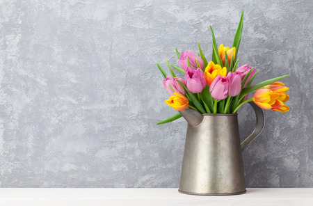 Fresh colorful tulip flowers bouquet in front of stone wall. View with copy space