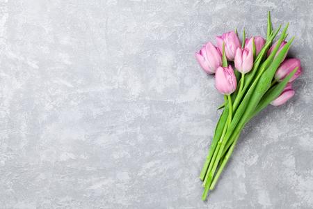 Verse roze tulp bloemen op stenen tafel. Bovenaanzicht met een kopie ruimte