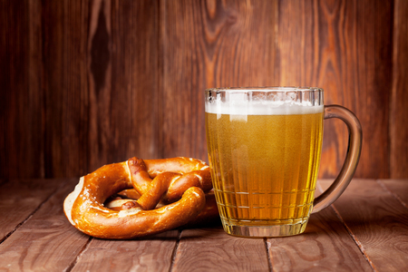 oktoberfest: Lager beer glass and pretzel on wooden table. View with copy space