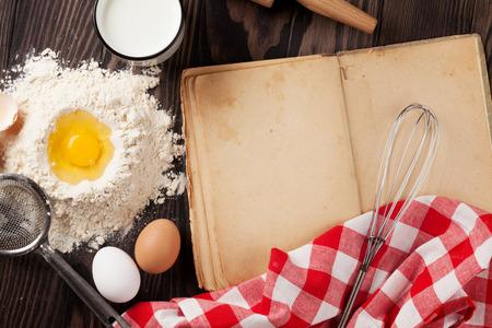 libros antiguos: Época en blanco en el libro de receta de cocina, utensilios e ingredientes en la mesa de madera. Vista superior con espacio de copia