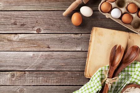 Keukentafel met kookboek, keukengerei en ingrediënten. Bovenaanzicht met een kopie ruimte