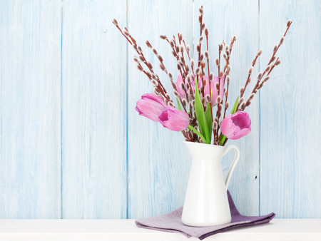 willows: Fresh pink tulip flowers bouquet on shelf in front of wooden wall. View with copy space