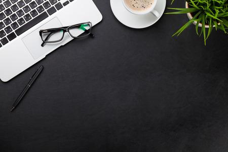 cuero de la oficina Mesa de trabajo con ordenador portátil, la taza de café y la planta. Vista superior con espacio de copia