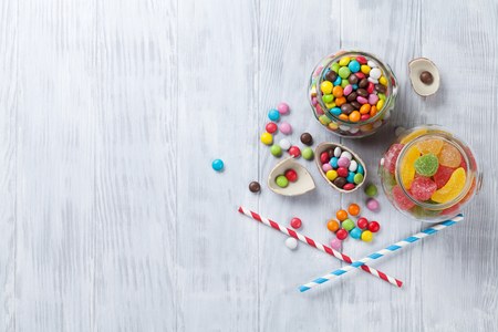 chocolate candy: Colorful candies on wooden table background. Top view with copy space