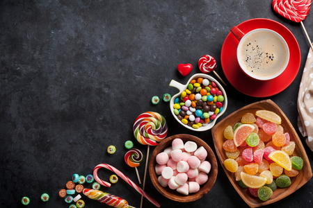 cafe bombon: Coffee, colorful candies, jelly and marmalade on stone background. Top view with copy space Foto de archivo