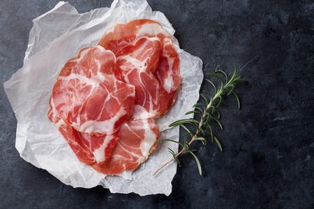 ham: Slices of prosciutto on paper over stone background. Top view with copy space