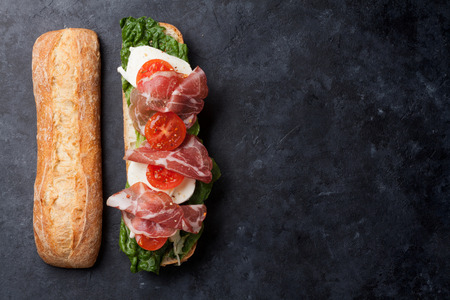 ingredient: Ciabatta sandwich with romaine salad, prosciutto and mozzarella cheese over stone background. Top view with copy space Stock Photo