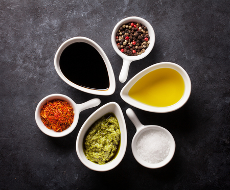 condiments: Condiments and spices on stone background. Top view