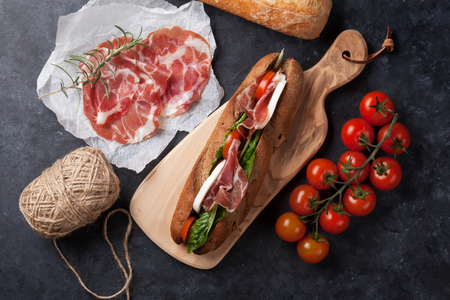 ingredient: Ciabatta sandwich with romaine salad, prosciutto and mozzarella cheese over stone background. Top view Stock Photo
