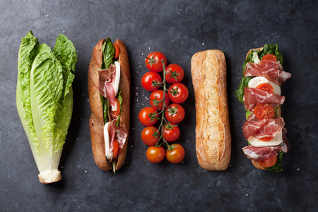 Ciabatta sandwich with romaine salad, prosciutto and mozzarella cheese over stone background. Top view Foto de archivo