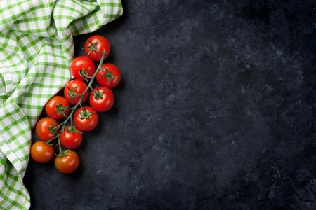 Rijpe kersen tomaten over steen keukentafel. Bovenaanzicht met een kopie ruimte Stockfoto