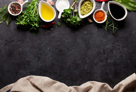 black stone: Herbs, condiments and spices on stone background. Top view with copy space