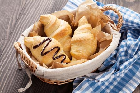wooden basket: Fresh croissants basket on wooden table Stock Photo