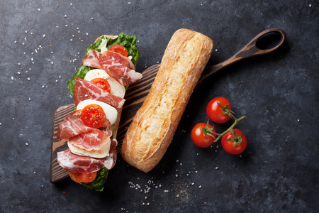 Ciabatta sandwich with romaine salad, prosciutto and mozzarella cheese on stone table. Top view