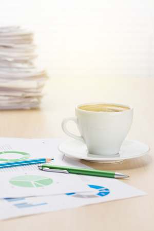 wood blinds: Office workplace with coffee cup, supplies and reports on wood desk table in front of window with blinds. View with copy space Stock Photo