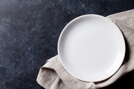 Empty plate and towel over stone table. Top view with copy space Stock Photo - 55955460