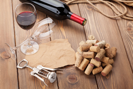 vino: Glass of red wine, bottle and corkscrew on rustic wooden table. Top view with copy space