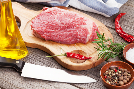 cutting board: Raw beef steak with spices and herbs on wooden table