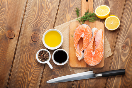 salmons: Salmon, spices and condiments on wooden table. Top view with copy space Stock Photo