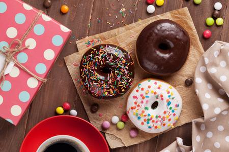 Donuts, Geschenkbox und Kaffee auf Holztisch. Draufsicht Standard-Bild