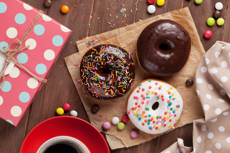 Donuts, gift box and coffee on wooden table. Top view Stock Photo
