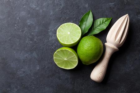 Limes en juicer op stenen achtergrond. Bovenaanzicht met kopie ruimte