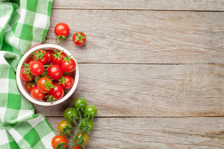 vegetables on white: Cherry tomatoes bowl on wooden table. Top view with copy space