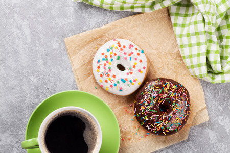 Colorful donuts and coffee on stone table. Top view with copy space Stock Photo - 56106863