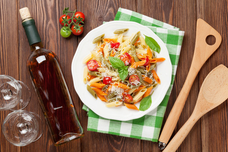 plato de comida: Colorful penne pasta and white wine on wooden table. Top view