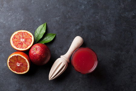 black stone: Red oranges and juice glass on stone background. Top view