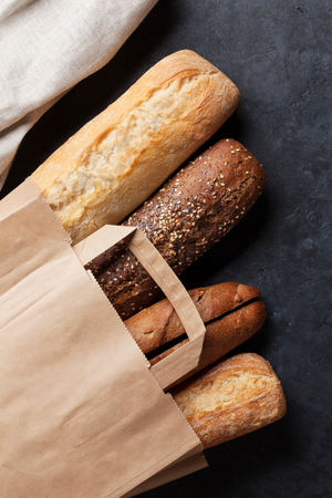paper bag: Mixed breads in paper bag on stone table. Top view