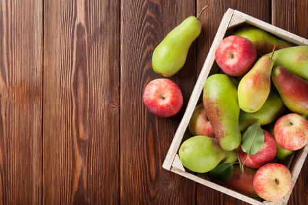 Pears and apples in wooden box on table. Top view with copy space