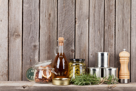 Cooking ingredients, herbs and spices on shelf against rustic wooden wall