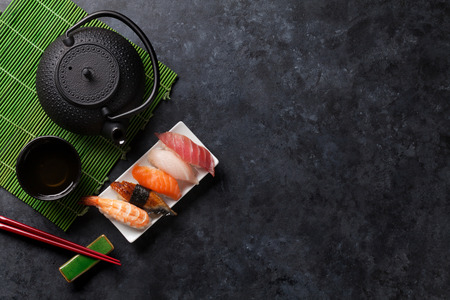 nigiri: Set of sushi and green tea on stone table. Top view with copy space