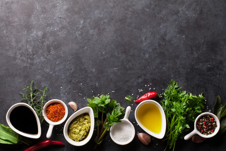 seasoning: Herbs, condiments and spices on stone background. Top view with copy space