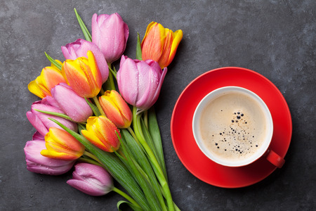 Fresh colorful tulip flowers and coffee cup on dark stone table. Top view Zdjęcie Seryjne