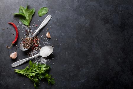 黒、白、赤唐辛子と塩スパイス スプーン。パセリとミントのハーブ。コピー スペース平面図 写真素材