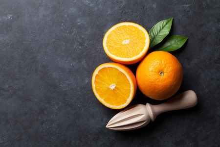 black stone: Oranges and juicer on stone background. Top view with copy space