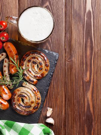 chorizos asados: salchichas a la parrilla y jarra de cerveza en la mesa de madera. Vista superior con espacio de copia Foto de archivo