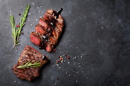 Gegrilltes Roastbeef in Scheiben geschnitten Steak mit Salz und Pfeffer über Steintisch. Ansicht von oben mit Kopie Raum Standard-Bild - 56448071