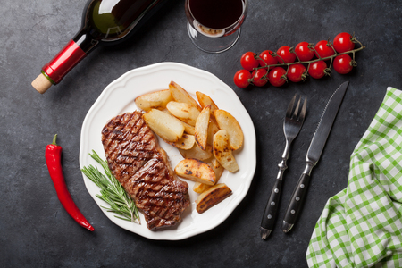 glass of red wine: Grilled striploin sliced steak and red wine over stone table. Top view Stock Photo
