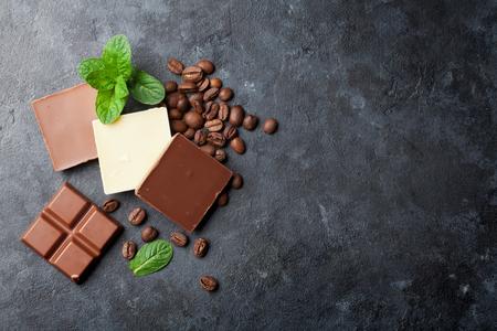 Schokolade und Kaffeebohnen auf dunklem Steintisch. Ansicht von oben mit Kopie Raum