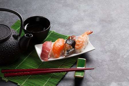 table set: Set of sushi and green tea on stone table. View with copy space