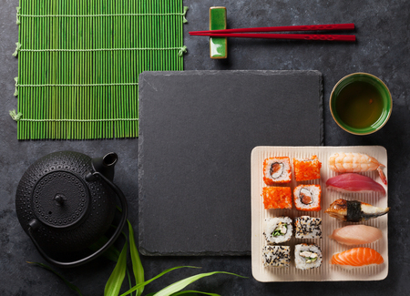 comida japonesa: Set of sushi, maki and green tea on stone table. Top view with copy space