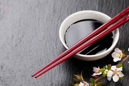 sauce bowl: Japanese sushi chopsticks, soy sauce bowl and sakura blossom on black stone background. Top view with copy space Stock Photo
