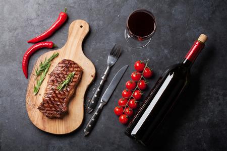 焼きサーロイン ステーキと赤ワインをスライスした石のテーブルの上。トップ ビュー