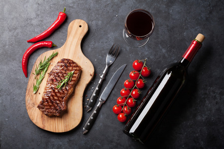 Grilled striploin sliced steak and red wine over stone table. Top view Stok Fotoğraf